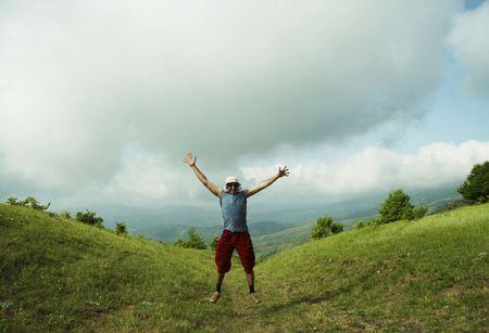 Jumping man on green hills Stock Photo - 959998