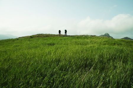 Two hikers on the green grassland in mountain photo
