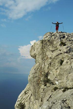 Joufull man on the rock cliff photo