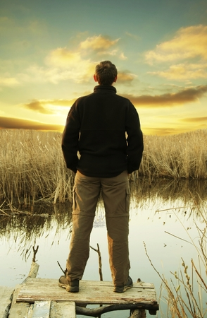 fishman: Man relaxing on sunset lake Stock Photo