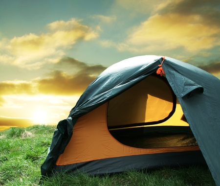 Green camping  tent on sunny grassland
