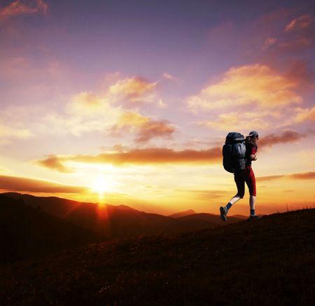 Girl going along hill on sunset photo