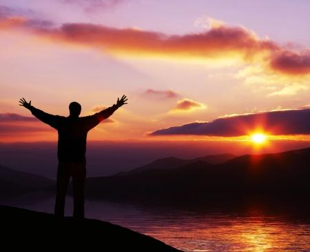 resurrecci�n: �hola d�a! Silueta feliz del hombre en salida del sol Foto de archivo