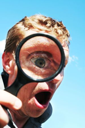 Astonished man see through magnifying glass photo