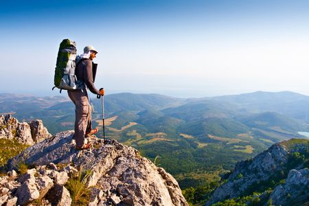 to observer: Male stand on the rock Stock Photo