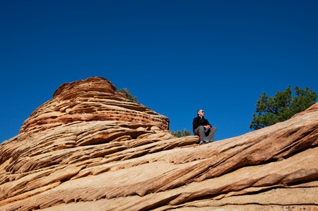 Men resting on cliff in Zion national park photo
