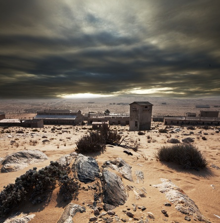 Ruins of abandoned houses in the ghost diamond town Kolmanskop, Namibia, Africa in storm photo