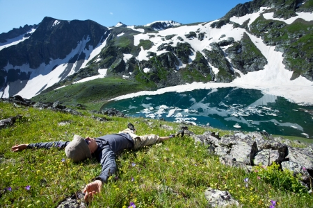 mountaineer: Man laying down near the mountains