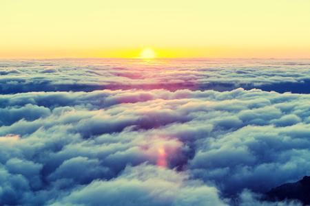 Prachtige zonsondergang op de heuvel boven de wolken Stockfoto