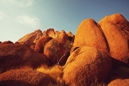 crack climb: Colorful landscapes of the orange rocks in the Spitscoppe mountains in Namibia on a sunny hot day.
