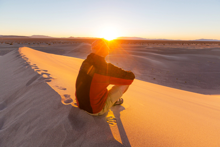 Hiker in sand desert. Sunrise time. photo