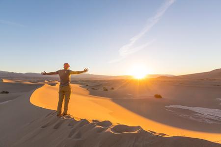 Hiker in sand desert. Sunrise time. Stock Photo