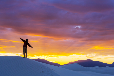 Hiker in sand desert. Sunrise time. Stock Photo