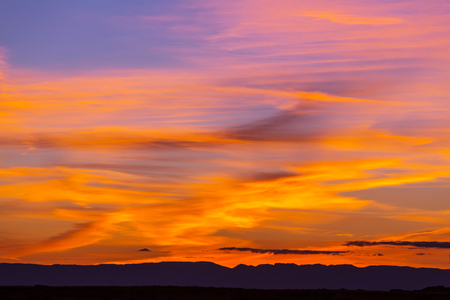 storm background: Unusual storm clouds at sunset. Bright red and orange colors of the sky. Suitable for background. Stock Photo