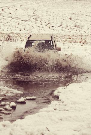 drive through: 4x4 vehicles drive through the water splashing in winter season Stock Photo