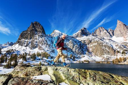 Man with hiking equipment walking in mountains,California,USA Stock Photo