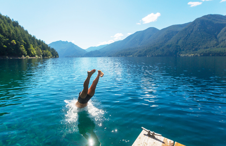 olympic national park: Man jumping in Crescent lake,Olympic National Park,Washington, USA Editorial