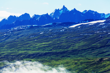 Picturesque Mountains of Alaska in summer. Snow covered massifs, glaciers and rocky peaks.