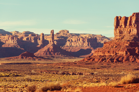 Valley of the Gods rock formation with Monument Valley at sunrise