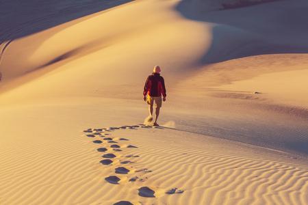 Hiker in sand desert. Sunrise time. photo