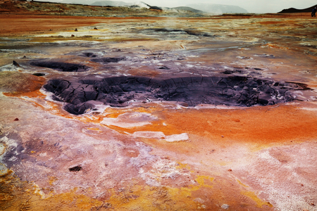 Boiling mud pools in a geothermal landscape in Iceland