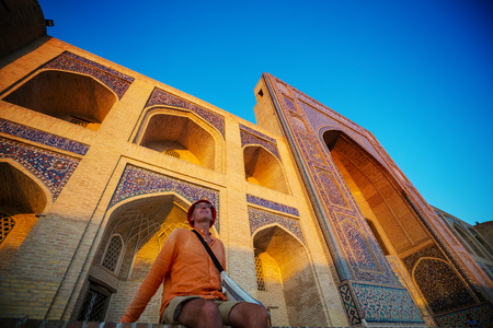 Tourist near ancient historic building in Uzbekistan