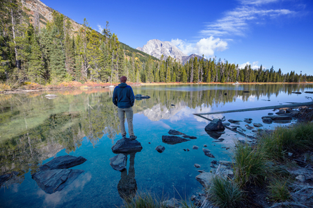Man on mountains lake in autumn season. Colorado, USA