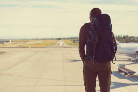 Backpacker near window in airport