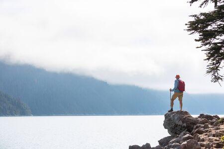 Hiker relaxing at serene mountain lake Banco de Imagens