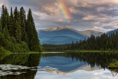 Serene scene by the mountain lake in Canada with reflection of the rocks in the calm water. 스톡 콘텐츠 - 128896672