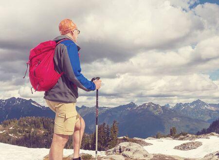 Mochilero en una caminata en las montañas de verano