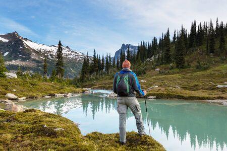 Hiker relaxing at serene mountain lake Stockfoto - 129704831