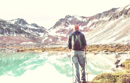 Hiker relaxing at serene mountain lake Stockfoto - 129705075