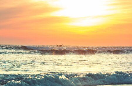Fishing boat in ocean at sunset