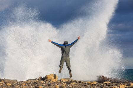Man jumping in dramatic storm waves