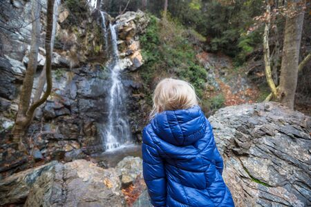 Little girl standing in front of waterfall. Happy emotion concept. 스톡 콘텐츠