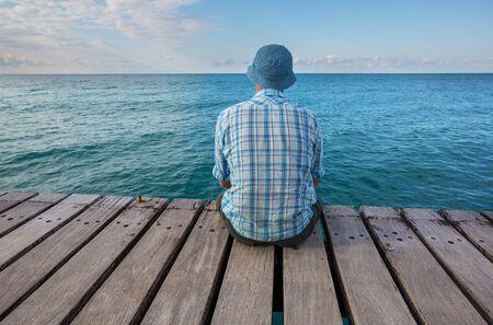 Man relaxing on sea pier