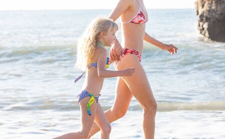 Family on the beach on sunset. Mother and daughter runing together.