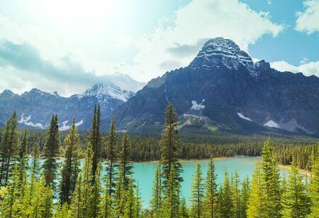 Escena serena por el lago de montaña en Canadá con reflejo de las rocas en las aguas tranquilas.