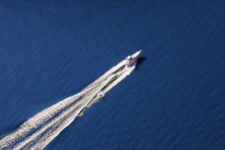 Aerial view of man wakeboarding on lake. Water skiing on lake behind a boat.