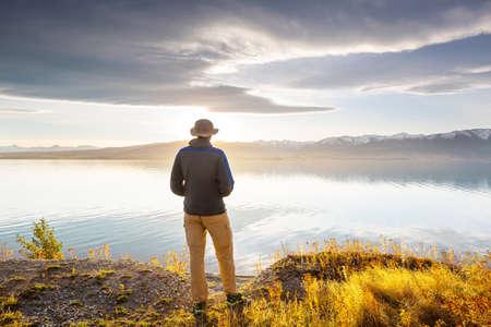 Man relaxing at beautiful  mountains lake. 免版税图像