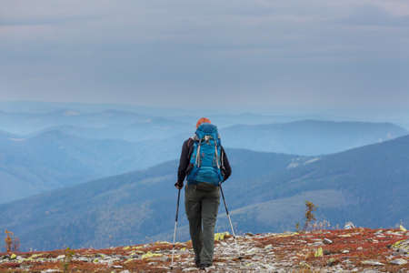 Backpacker in hike in the high mountains