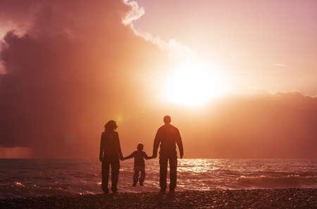 Family on the beach on sunset. Standard-Bild