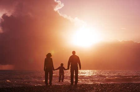 Family on the beach on sunset. Banque d'images