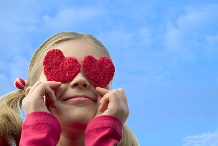 girl with red hearts against blue sky Stock Photo