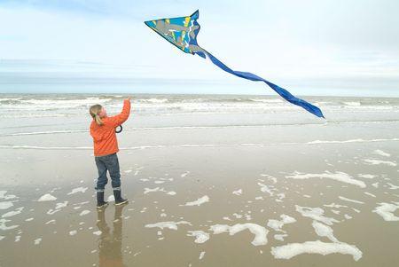 junges M�dchen, das einen Drachen auf dem Strand fliegt