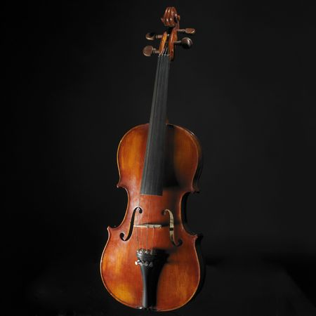 Old violin against black background
