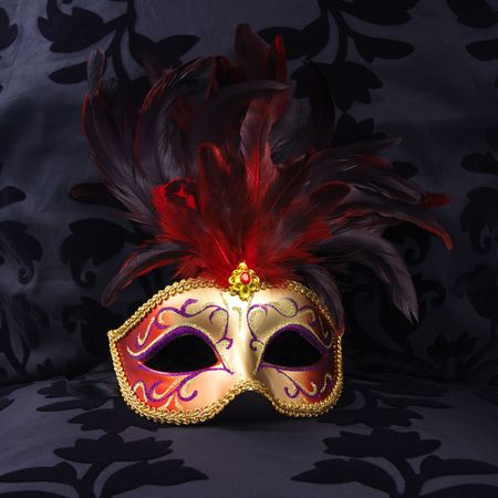 golden and red colored mask at a black velvet seat  (Venice, Italy) Stock Photo