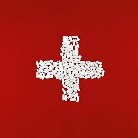 Kreuz aus wei�em Pillen auf einem roten Hintergrund Kreide