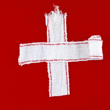 cross made of white bandages on a red chalk background photo